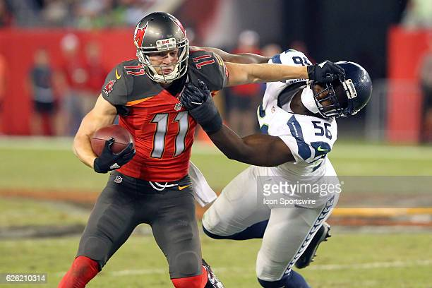 Adam Humphries of the Buccaneers gives a still arm to Cliff Avril of the Seahawks during the NFL Game between the Seattle Seahawks and Tampa Bay...