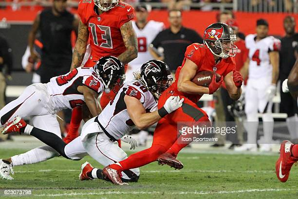 Adam Humphries of the Buccaneers makes a catch and then run as Brooks Reed of the Falcons tries the bring Humphries down during the NFL game between...