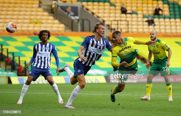 Adam Idah of Norwich City shoots a header while under pressure from Dan Burn of Brighton and Hove Albion during the Premier League match between...