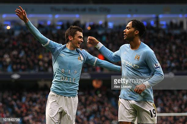 Adam Johnson of Manchester City celebrates with Joleon Lescott after scoring the opening goal during the Barclays Premier League match between...