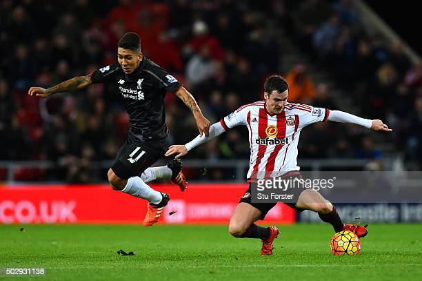 Adam Johnson of Sunderland battles for the ball with Roberto Firmino of Liverpool during the Barclays Premier League match between Sunderland and...