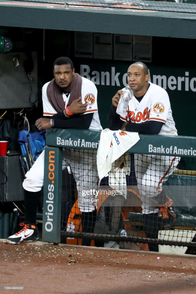 Adam Jones #10 and Jonathan Schoop #6 of the Baltimore Orioles look on from the dugout in the eighth inning against the Boston Red Sox at Oriole Park at Camden Yards on July 23, 2018 in Baltimore, Maryland.