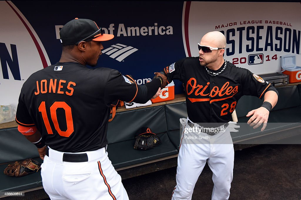 Adam Jones #10 and Steve Pearce #28 of the Baltimore Orioles celebrate in the dugout during Game Two of the American League Division Series against the Detroit Tigers at Oriole Park at Camden Yards on October 3, 2014 in Baltimore, Maryland.