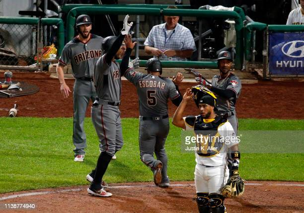 Adam Jones Jarrod Dyson and Eduardo Escobar of the Arizona Diamondbacks celebrate after scoring on a three RBI triple in the seventh inning against...
