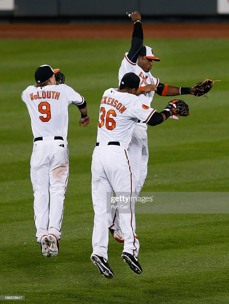 Adam Jones #10, Nate McLouth #9, and Chris Dickerson #36 of the Baltimore Orioles celebrate after the Orioles defeated the Kansas City Royals 5-3 at Oriole Park at Camden Yards on May 8, 2013 in Baltimore, Maryland.