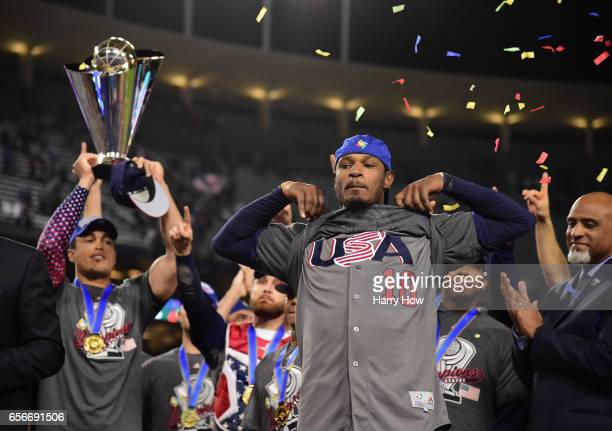 Adam Jones of team United States shoes his USA shirt while teammate Giancarlo Stanton holds the trophy after their 80 win over team Puerto Rico...