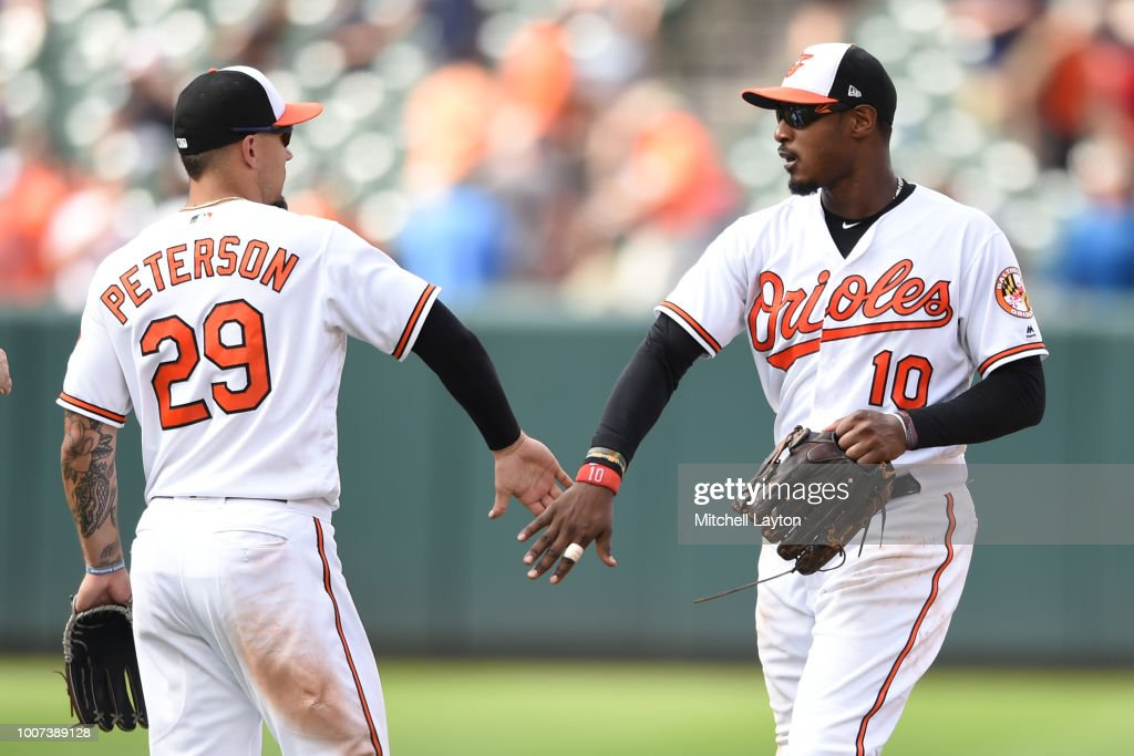 Adam Jones #10 of the Baltimore Orioles celebrates a win with Jace Peterson #29 after a baseball game against the Tampa Bay Rays at Oriole Park at Camden Yards on July 29, 2018 in Baltimore, Maryland.
