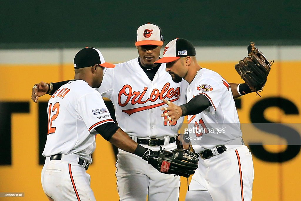 Adam Jones #10 of the Baltimore Orioles celebrates with Alejandro De Aza #12 and Nick Markakis #21 after defeating the Detroit Tigers 12-3 in Game One of the American League Division Series at Oriole Park at Camden Yards on October 2, 2014 in Baltimore, Maryland.