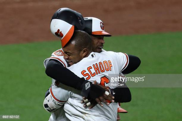 Adam Jones of the Baltimore Orioles celebrates with Jonathan Schoop after scoring the winning run in the tenth inning to give the Orioles a 65 win...