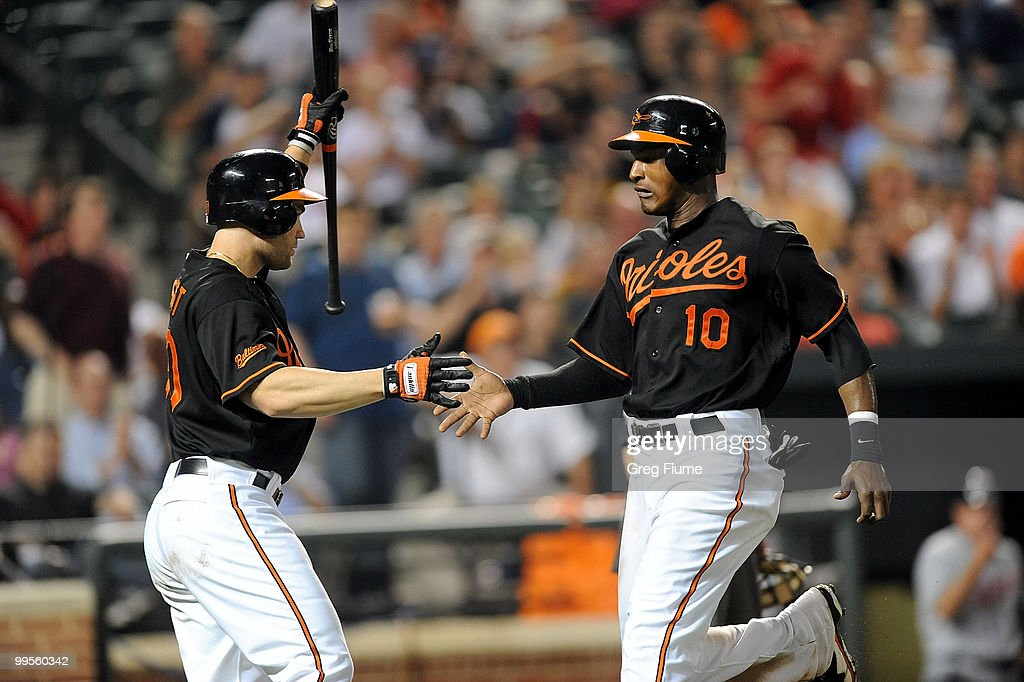 Adam Jones #10 of the Baltimore Orioles celebrates with Luke Scott #30 after scoring in the seventh inning against the Cleveland Indians at Camden Yards on May 14, 2010 in Baltimore, Maryland.