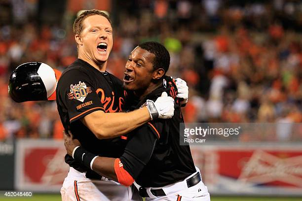 Adam Jones of the Baltimore Orioles celebrates with teammate Nick Hundley after Hundley hit the game winning single to give the Orioles a 3-2 win...