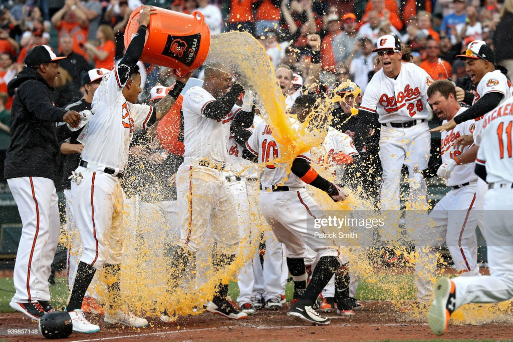 Adam Jones #10 of the Baltimore Orioles celebrates with teammates after hitting a walk-off home run against the Minnesota Twins during the eleventh inning in their Opening Day game at Oriole Park at Camden Yards on March 29, 2018 in Baltimore, Maryland.