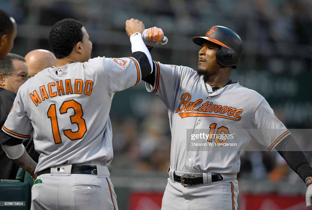 Adam Jones #10 of the Baltimore Orioles is congratulated by Manny Machado #13 after Jones hit a solo home run against the Oakland Athletics in the top of the fourth inning at Oakland Alameda Coliseum on August 10, 2017 in Oakland, California.