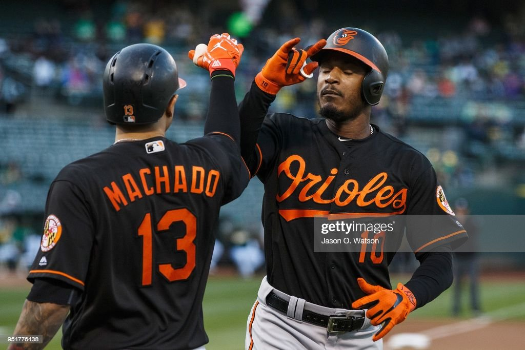Adam Jones #10 of the Baltimore Orioles is congratulated by Manny Machado #13 after hitting a home run against the Oakland Athletics during the first inning at the Oakland Coliseum on May 4, 2018 in Oakland, California.