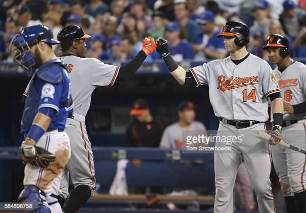 Adam Jones of the Baltimore Orioles is congratulated by Nolan Reimold and Jonathan Schoop after hitting a threerun home run in the twelfth inning...