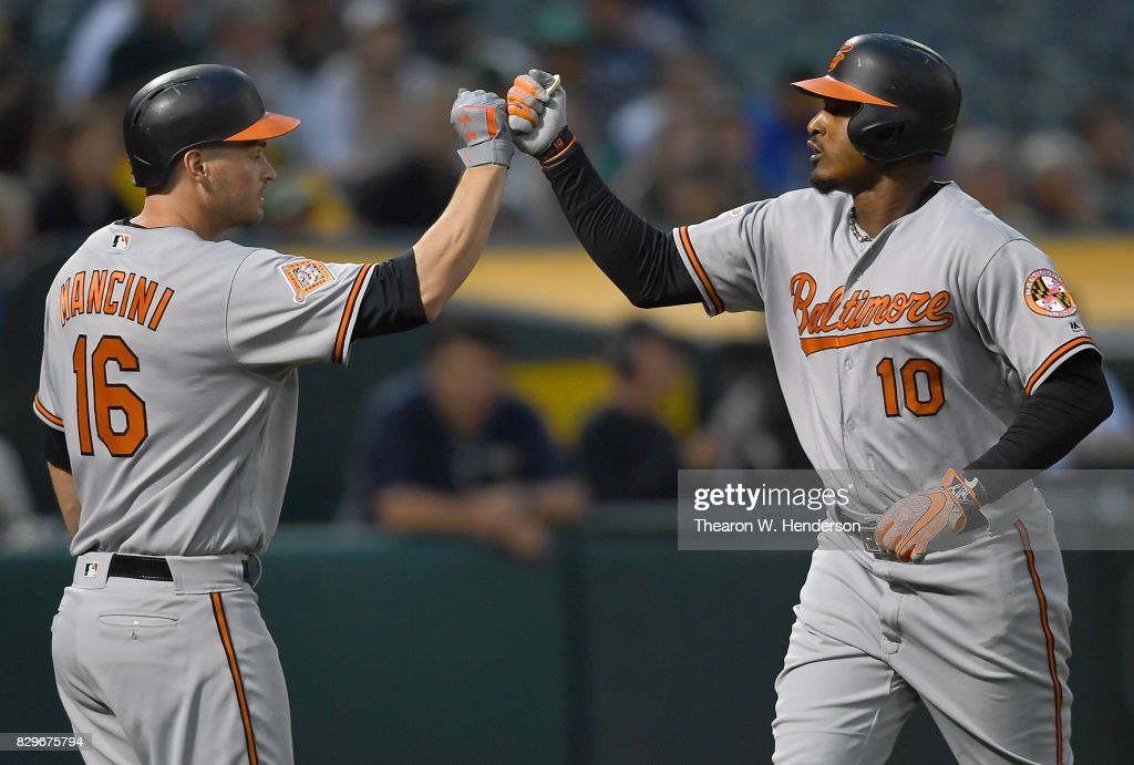 Adam Jones #10 of the Baltimore Orioles is congratulated by Trey Mancini #16 after Jones hit a solo home run against the Oakland Athletics in the top of the fourth inning at Oakland Alameda Coliseum on August 10, 2017 in Oakland, California.