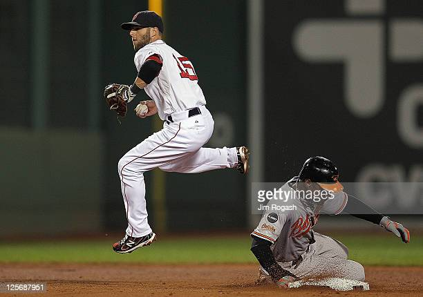 Adam Jones of the Baltimore Orioles is out at second as Dustin Pedroia of the Boston Red Sox turns a double play in the second inning at Fenway Park...