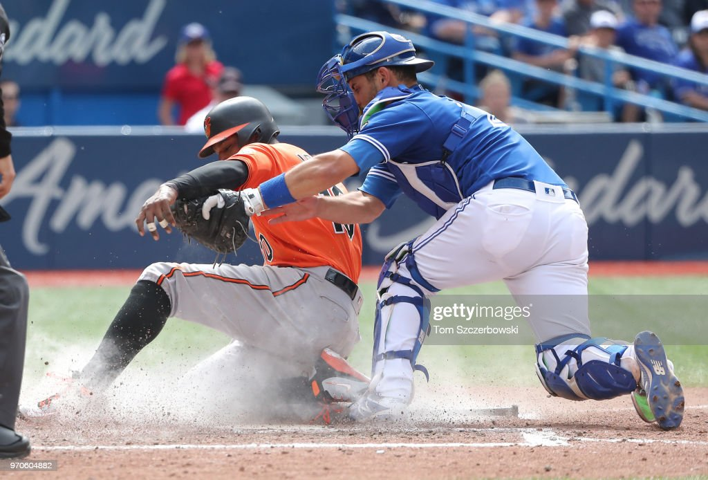 Adam Jones #10 of the Baltimore Orioles is tagged out at home plate trying to score in the ninth inning during MLB game action as Luke Maile #21 of the Toronto Blue Jays tags him out at Rogers Centre on June 9, 2018 in Toronto, Canada.