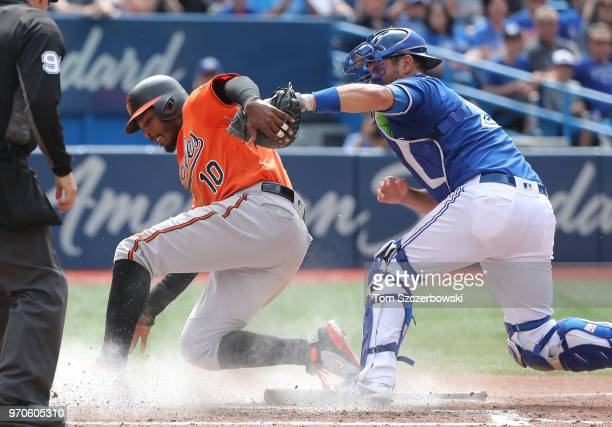 Adam Jones of the Baltimore Orioles is tagged out at home plate trying to score in the ninth inning during MLB game action as Luke Maile of the...