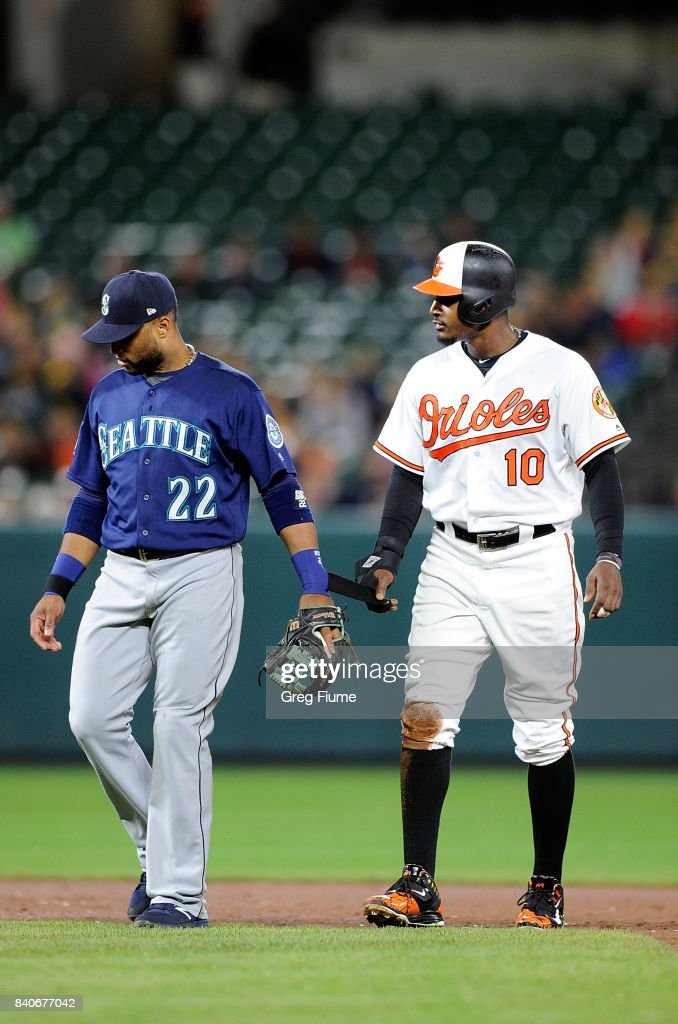 Adam Jones #10 of the Baltimore Orioles pulls on the wristband of Robinson Cano #22 of the Seattle Mariners in the eighth inning at Oriole Park at Camden Yards on August 29, 2017 in Baltimore, Maryland.