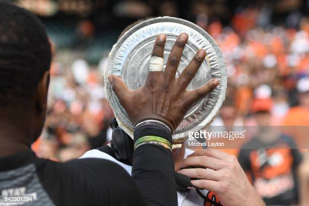 Adam Jones of the Baltimore Orioles puts a pie in the face of Mark Trumbo after after hitting game winning hit in the 12th inning during a baseball...