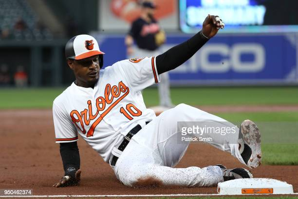Adam Jones of the Baltimore Orioles slides into third base after advancing bases on a hit by teammates Chris Davis against the Cleveland Indians...