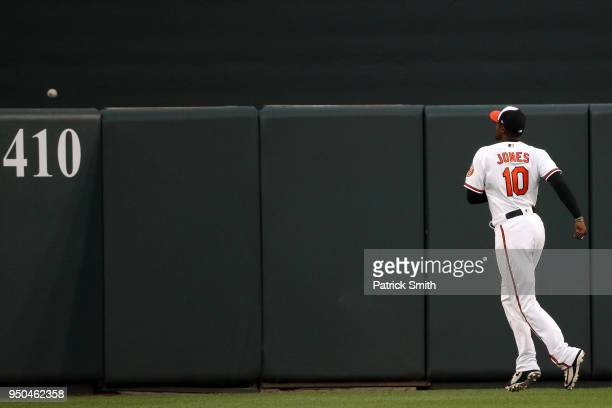 Adam Jones of the Baltimore Orioles watches a home run hit by Yonder Alonso of the Cleveland Indians go over the outfield wall during the second...