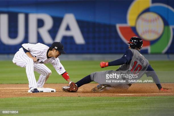 Adam Jones of the United States is tagged out by Infielder Hayato Sakamoto of Japan as he fails to steal base in the top of the sixth inning during...