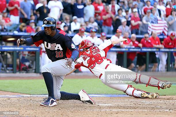 Adam Jones of USA scores a run past catcher Chris Robinson of Canada during the eighth inning of the World Baseball Classic First Round Group D game...
