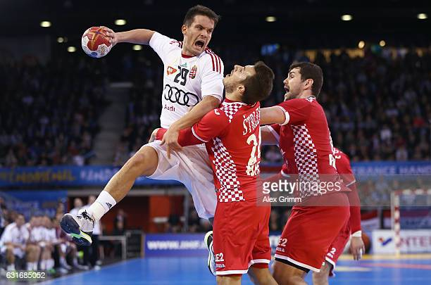 Adam Juhasz of Hungary is challenged by Manuel Strlek and Jakov Gojun of Croatia during the 25th IHF Men's World Championship 2017 match between...