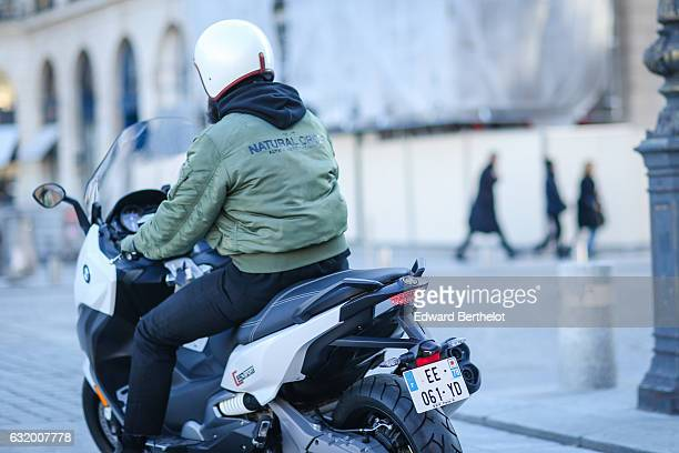 Adam Katz Sinding photographer from the blog Le 21eme is wearing a green bomber jacket with the inscription Natural Order and is riding a BMW...