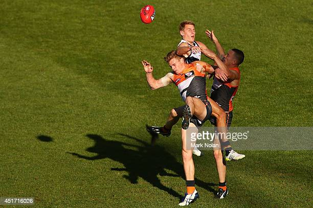 Adam Kennedy and Tom Scully of the Giants and David Mackay of the Crows contest a mark during the round 16 AFL match between the Greater Western...