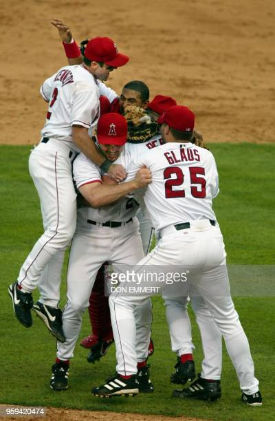 Adam Kennedy of the Anaheim Angels leaps onto his teammates after they defeated the Minnesota Twins 13 October 2002 during game five of the American...