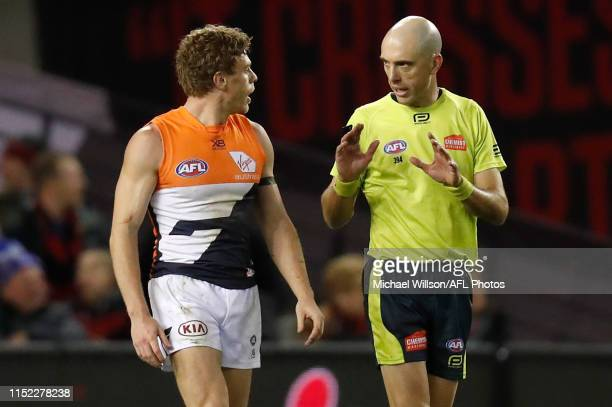 Adam Kennedy of the Giants speaks with AFL Field Umpire Mathew Nicholls during the 2019 AFL round 15 match between the Essendon Bombers and the GWS...