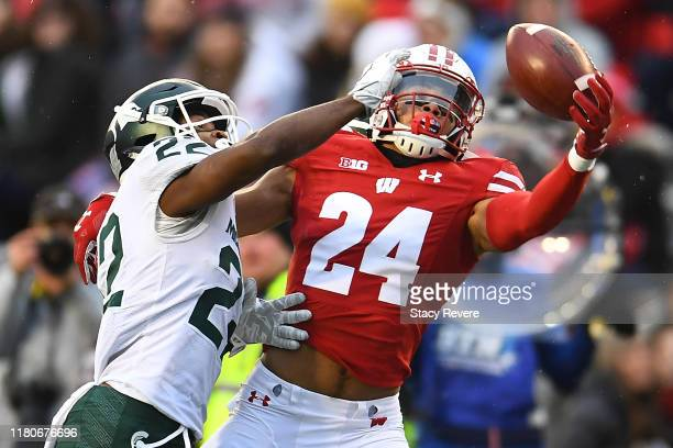 Adam Krumholz of the Wisconsin Badgers is defended by Josiah Scott of the Michigan State Spartans during the second half of a game at Camp Randall...