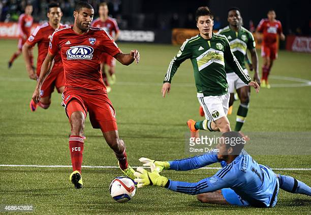 Adam Kwarasey of Portland Timbers dives to stop the ball as Tesho Akindele of FC Dallas closes in during the first half of the game at Providence...