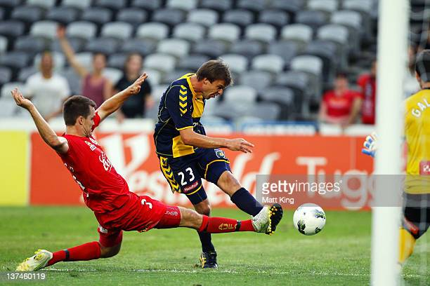 Adam Kwasnik of the Mariners beats Nigel Boogaard of United to score a goal during the round 16 A-League match between the Central Coast Mariners and...