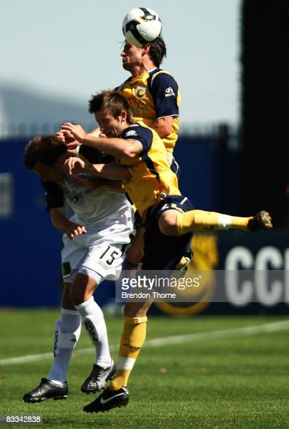 Adam Kwasnik of the Phoenix competes with Matthew Osman and Andrew Clark of the Mariners during the round eight A-League match between the Central...