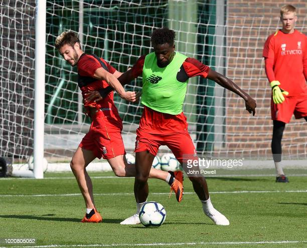Adam Lallana and Divock Origi of Liverpool during a training session at Melwood Training Ground on August 21 2018 in Liverpool England