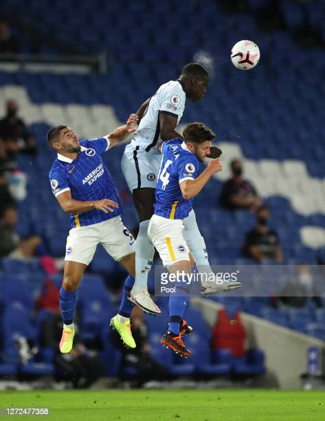 Adam Lallana and Neal Maupay of Brighton and Hove Albion jump for the ball with Kurt Zouma of Chelsea during the Premier League match between...
