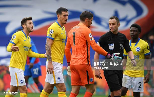 Adam Lallana Lewis Dunk and Matthew Ryan of Brighton and Hove Albion complain to referee Stuart Attwell after he gives a penalty during the Premier...