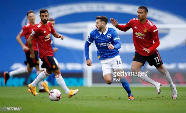 Adam Lallana of Brighton and Hove Albion is challenged by Mason Greenwood of Manchester United during the Premier League match between Brighton Hove...