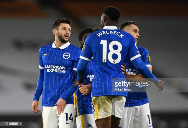 Adam Lallana of Brighton and Hove Albion looks over to the referee whilst he celebrates with teammates Danny Welbeck and Leondro Trossard after...