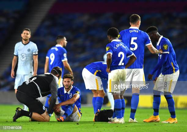 Adam Lallana of Brighton and Hove Albion receives medical attention for an injury during the Premier League match between Brighton Hove Albion and...