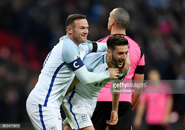 Adam Lallana of England celebrates with Wayne Rooney as he scores their second goal during the FIFA 2018 World Cup qualifying match between England...