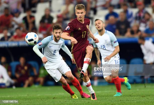 Adam Lallana of England challenges for the ball with Oleg Shatov of Russia during the UEFA Euro 2016 Group B soccer match between England and Russia...