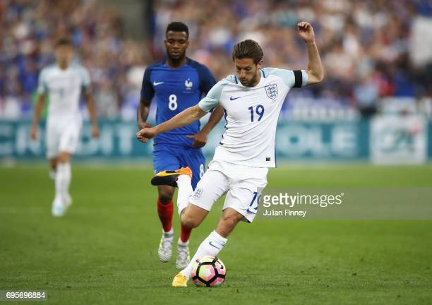 Adam Lallana of England is watched by Thomas Lemar of France during the International Friendly match between France and England at Stade de France on...