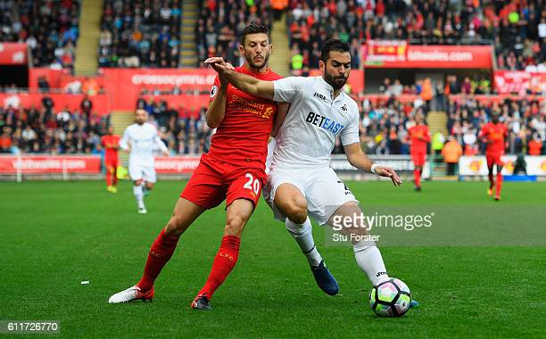 Adam Lallana of Liverpool and Jordi Amat of Swansea City battle for possession during the Premier League match between Swansea City and Liverpool at...