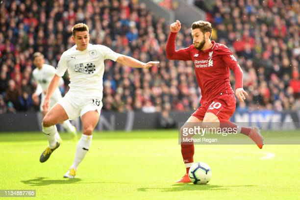 Adam Lallana of Liverpool avoids a challenge from Ashley Westwood of Burnley during the Premier League match between Liverpool FC and Burnley FC at...