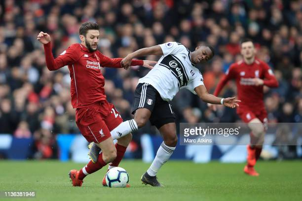 Adam Lallana of Liverpool battles for possession with Floyd Ayite of Fulham during the Premier League match between Fulham FC and Liverpool FC at...